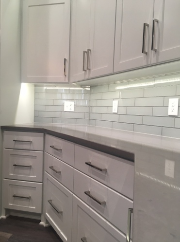 Under cabinet lighting and a beautiful backsplash.