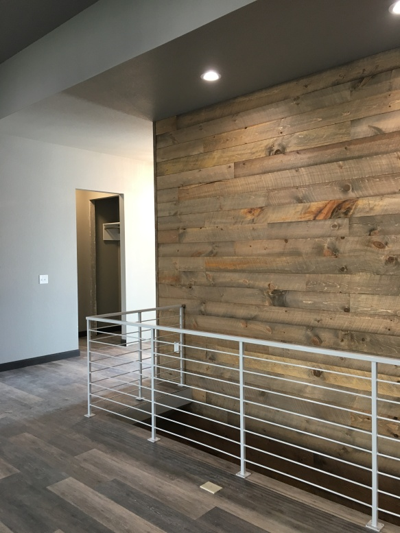 A reclaimed wood feature wall marks the middle of the living space and flows into the lower level.